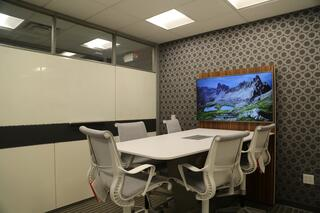 """One of our """"quick standup"""" rooms outfitted with a standing height table and a TV for sharing"""