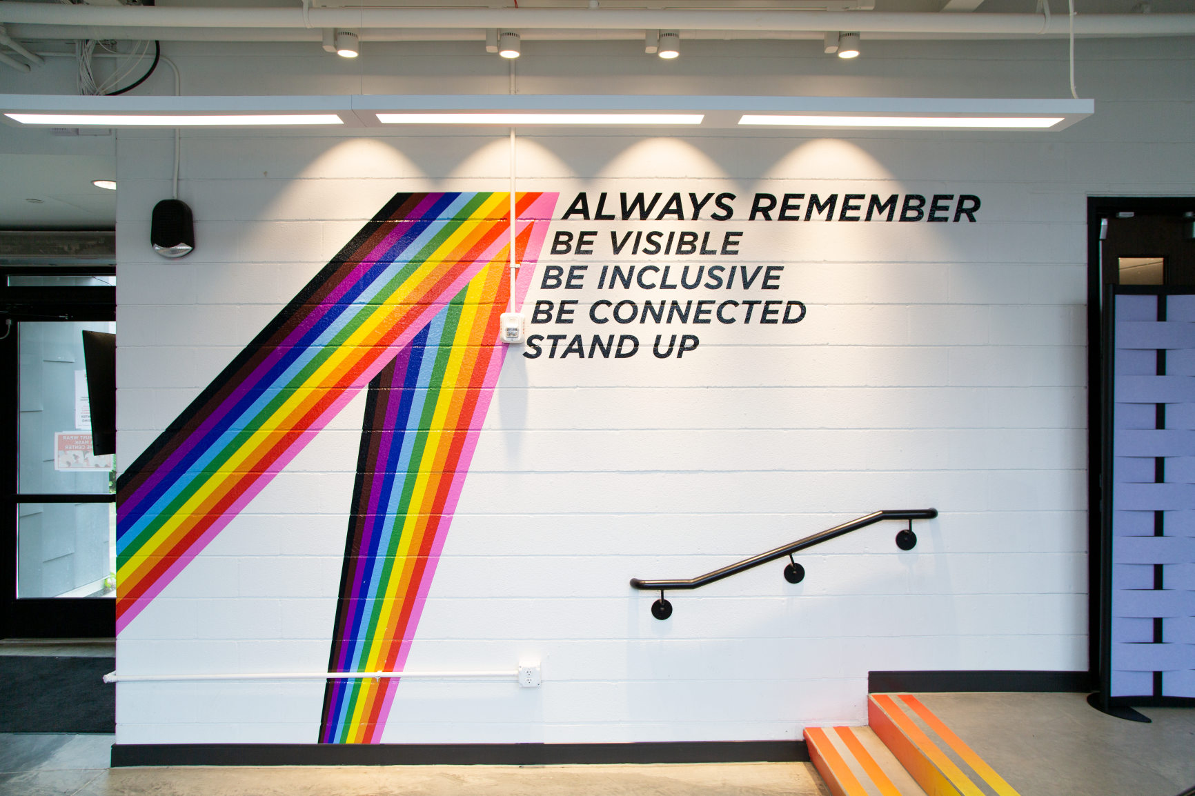 A rainbow vinyl graphic brings this space to life at Stonewall Columbus Community Center by Continental Office Branding