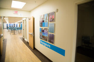 "A ""Voyageurs"" wall features photos of students' travels"